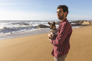 Portugal, Porto, young man on the beach with his dog - WPEF01524