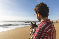 Portugal, Porto, young man with dog on his arms looking at the sea - WPEF01527