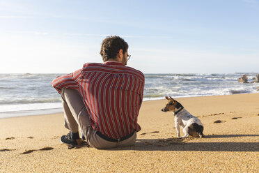 Portugal, Porto, back view of young man sitting on the beach with his dog - WPEF01530