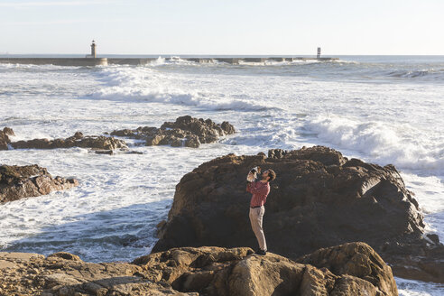 Portugal, Porto, young man standing on rock with his dog - WPEF01533