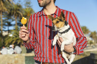 Young man with dog on his arm eating ice lolly, partial view - WPEF01536