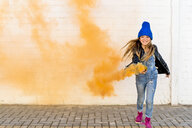 Portrait of smiling girl with orange smoke torch - ERRF01277