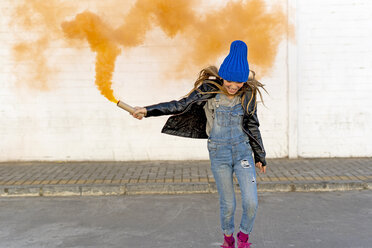 Smiling girl with orange smoke torch on the street - ERRF01280