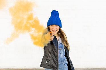 Portrait of smiling girl with orange smoke torch pointing on viewer - ERRF01286