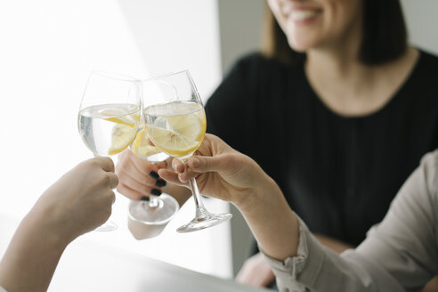 Close-up of three women toasting glasses of water - AHSF00349