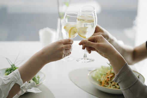 Close-up of three women toasting glasses of water in a restaurant - AHSF00352