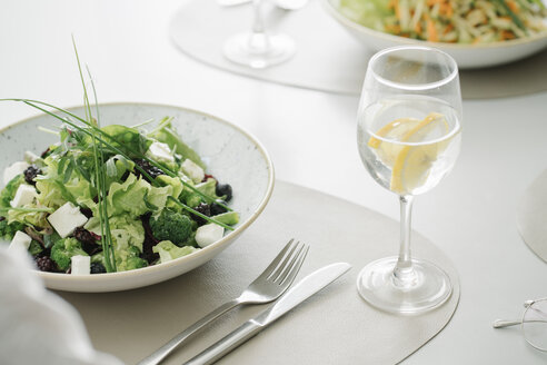 Salad and glass of water on a table in a restaurant - AHSF00358