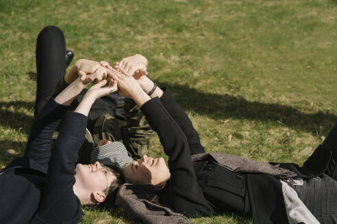 Group of young women lying in grass putting their hands together - AHSF00367