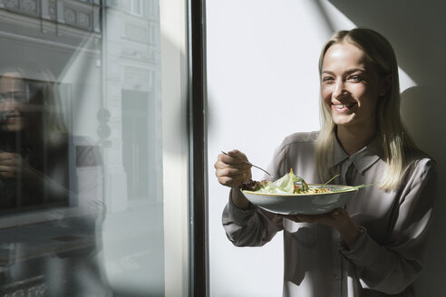 Smiling young woman standing at the window in sunshine eating a salad - AHSF00382