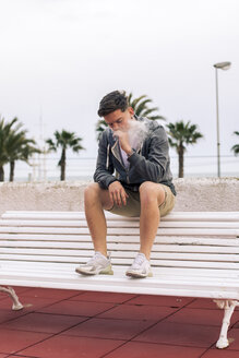 Boy smoking a joint sitting in a bank with palm trees in the background - ACPF00508