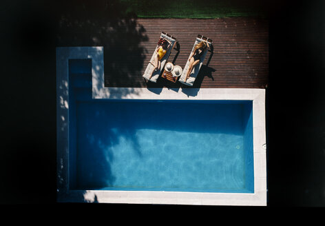Two beautiful women sunbathing on a terrace next to the pool - OCMF00450
