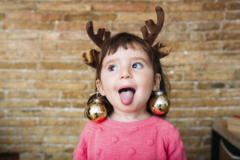 Portrait of toddler girl sticking out tongue wearing reindeer antlers headband and Christmas baubles - GEMF02944