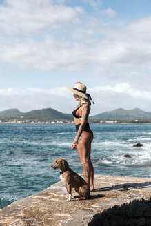 Tattooed woman in a black bikini and hat looking at the sea with her brown dog. Mallorca, Balearic Islands, Spain. - LOTF00069