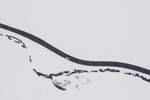 Österreich, Tirol, Galtür, Blick von oben auf eine Landstrasse und einen Fluss umgeben von Tiefschnee im Winter. Luftaufnahme, Drohnenaufahme, Textfreiraum, directly above. - MMAF00951