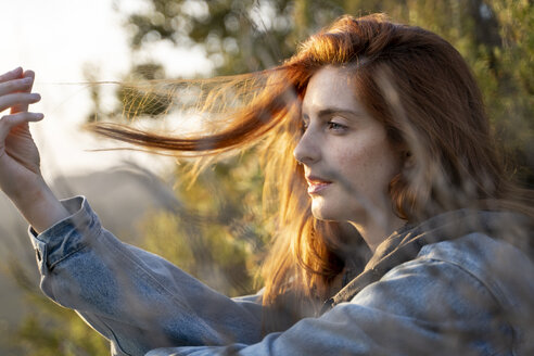 Redheaded young woman in nature at sunset - AFVF02940