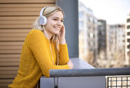 Portrait of smiling young woman listening music with headphones - BFRF02009