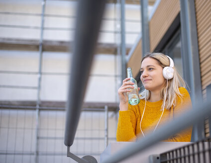 Smiling young woman with soft drink listening music with headphones - BFRF02012