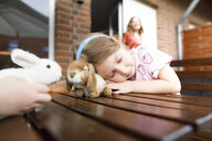 Girl lying on garden table with toy bunny - KMKF00950