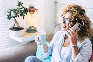 Woman on couch at home with coffee mug on cell phone - SIPF01954