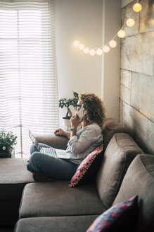 Woman on couch at home with laptop and cell phone - SIPF01963