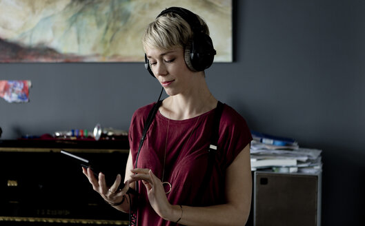 Portrait of blond woman listening music with headphones and digital tablet - FLLF00133