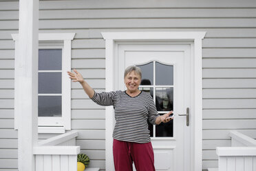 Happy senior woman standing on porch of her house - KMKF00967