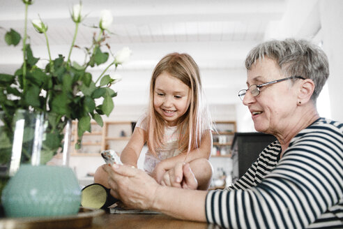 Happy grandmother with cell phone and granddaughter at home - KMKF00970