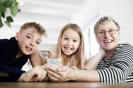 Portrait of happy grandmother and grandchildren with cell phone at home - KMKF00973