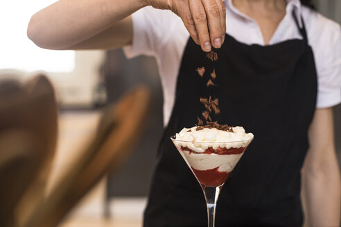 Close-up of woman pouring chocolate on a dessert in kitchen - ABZF02376