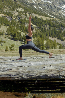 Young woman doing yoga on tree trunks in nature, warrior pose - JPF00387