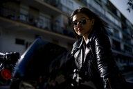 Portrait of content young woman on motorbike - OCMF00456