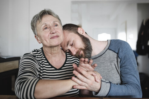 Affectionate adult son with senior mother at home - KMKF00975