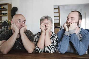 Portrait of adult sons with senior mother sitting at table at home with head in hands - KMKF00981