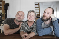 Portrait of smiling adult sons with senior mother at home - KMKF00984