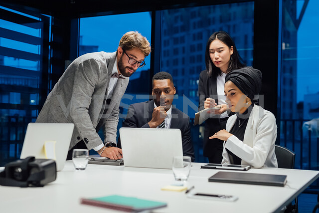 Businesswomen and men looking at laptop during conference table meeting - CUF51316