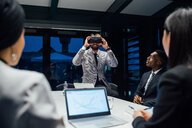 Businessman looking through virtual reality headset during conference table meeting - CUF51319
