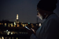 Young businesswoman looking smartphone on office balcony at night - CUF51331