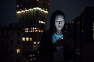 Young businesswoman looking smartphone on office balcony at night - CUF51334
