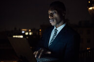 Young businessman typing on laptop on office balcony at night, close up - CUF51337