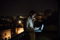 Mid adult businessman looking at smartphone on office balcony at night - CUF51340