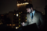 Mid adult businessman looking at smartphone on office balcony at night - CUF51343
