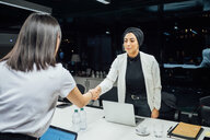Businesswomen shaking hands over conference table - CUF51358