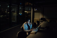 Young businesswoman in office at night typing on laptop - CUF51361