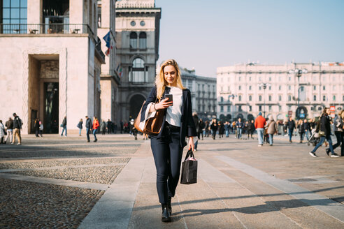 Young female tourist with shopping bags strolling and looking at smartphone in city square, Milan, Italy - CUF51376