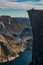 Hiker enjoying view on cliff top, Preikestolen (Pulpit Rock), Lysefjord, Norway, Stavanger - CUF51391