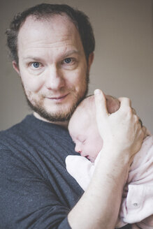 Portrait of father holding his sleeping newborn baby daughter - IHF00010