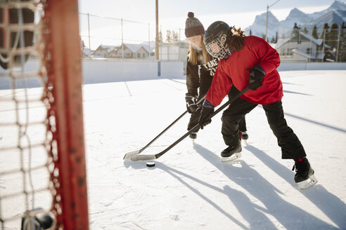 Mother and daughter playing outdoor ice hockey - HEROF36202