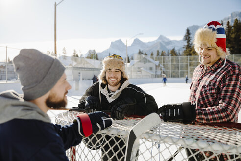 Male friends playing outdoor ice hockey, talking at goal - HEROF36205
