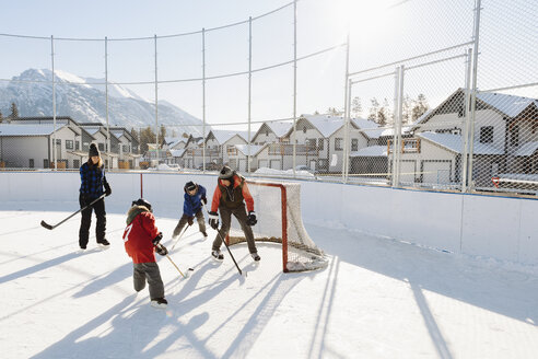 Family playing outdoor ice hockey - HEROF36226