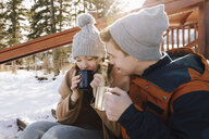 Affectionate young couple drinking hot chocolate on snowy steps - HEROF36244